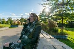 Schöne glückliche lächelnde junge Frau, die Handy verwendet lizenzfreies stockfoto