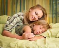 Schöne glückliche lächelnde Mutter, die ihre nette Tochter schläft im Bett umfasst Stockbilder