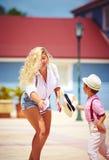 Schöne glückliche Mutter, die mit Sohn auf karibischer Straße spielt Stockbilder