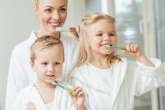 schöne glückliche Mutter und Kinder beim Bademantelbürsten stockfotografie