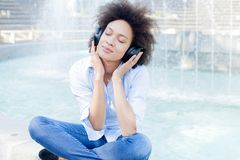 Schöne glückliche schwarze junge Frauen-hörende Musik lizenzfreies stockbild