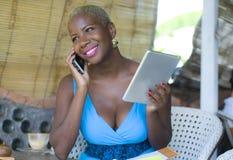 Schöne glückliche und beschäftigte schwarze afroe-amerikanisch Frau, die an der Kaffeestube spricht auf Handyvernetzung auf digit stockfotografie