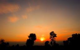 Schöne glühende Sonnenunterganglandschaft über an der Wiese und am orange Himmel über ihm Erstaunlicher Sommersonnenaufgang als H Lizenzfreies Stockbild