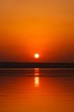 Schöne glühende Sonnenunterganglandschaft am Fluss Dnipro und am orange Himmel über ihm mit goldener Reflexion der ehrfürchtigen  Stockfotos