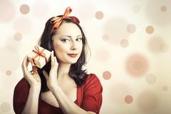 Schöne gorgerous Brunettefrau, die eine rote Bandgeschenkbox hält Lizenzfreies Stockbild