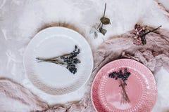 Schöne graue und rosa keramische Platten mit einem Blumenstrauß des Lavendels, rosa Gaze auf grauem konkretem Hintergrund lizenzfreie stockfotos