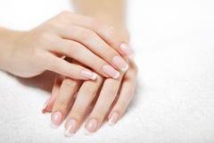 Schöne Hände auf dem weißen Tuch Lizenzfreies Stockbild