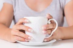 Schöne Hände der jungen Frau mit natürlichen Nägeln maniküren das Halten des Tasse Kaffees lizenzfreie stockfotografie