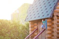 Schöne hölzerne Hütte im Garten Kleines rustikales Blockhaus für Kinderspiele Bunter Eisenjunger hahn nahe Eingang Sonnenuntergan Stockbild