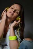 Schöne hörende Musik der jungen Frau stockfotografie
