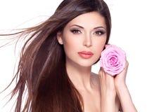 Schöne hübsche Frau mit langer Haar- und Rosarose am Gesicht. Lizenzfreie Stockfotografie