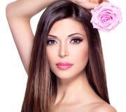 Schöne hübsche Frau mit langer Haar- und Rosarose am Gesicht Stockbild