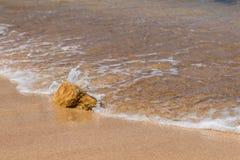 Schöne haarscharfe Seewelle, die über Felsen auf goldenem s spritzt Stockfotografie