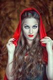Schöne Halloween-Frau im roten Mantel stockbilder