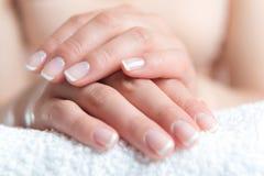 Schöne Hand mit französischer Maniküre des perfekten Nagels Stockfotografie
