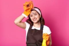 Schöne Hausfrau, die mit der Hand berührt Kopf, Holdingreinigungsmittel, herzlichst lächelnd aufwirft und haben angenehmen Gesich lizenzfreies stockfoto