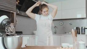 Schöne Hausfrau sammelt ihr Haar in einem Pferdeschwanz Bereiten Sie sich zum Kochen von Kuchen vor stock video