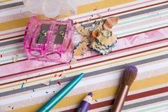 Schöne helle Lidschatten, Make-up, Bleistiftspitzer, Bürste auf einem hellen farbigen Hintergrund, weiche Bettwäschefarben Stockfotos