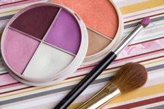 Schöne helle Lidschatten, Make-up, Bleistiftspitzer, Bürste auf einem hellen farbigen Hintergrund, weiche Bettwäschefarben Lizenzfreie Stockfotografie