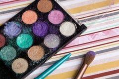 Schöne helle Lidschatten, Make-up, Bleistiftspitzer, Bürste auf einem hellen farbigen Hintergrund, weiche Bettwäschefarben Stockfoto