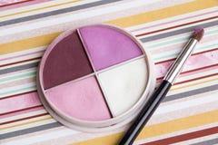 Schöne helle Lidschatten, Make-up, Bleistiftspitzer, Bürste auf einem hellen farbigen Hintergrund, weiche Bettwäschefarben Stockbild