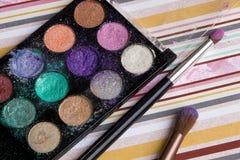 Schöne helle Lidschatten, Make-up, Bleistiftspitzer, Bürste auf einem hellen farbigen Hintergrund, weiche Bettwäschefarben Lizenzfreie Stockfotos