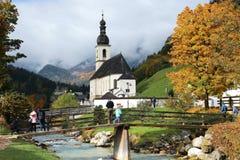 Schöne Herbstahornbäume durch den Strom und eine Holzbrücke vor einer Kirche mit nebeligen Bergen im entfernten Hintergrund Lizenzfreie Stockfotos