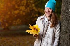 Schöne Herbstfrau mit gelben Fallblättern Stockfoto