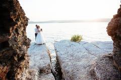 Schöne herrliche blonde Braut und stilvoller Bräutigam auf Felsen Stockbild