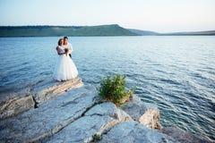 Schöne herrliche blonde Braut und stilvoller Bräutigam auf Felsen Stockfotografie
