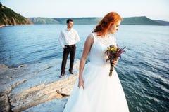 Schöne herrliche blonde Braut und stilvoller Bräutigam auf Felsen Stockbilder