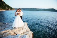 Schöne herrliche blonde Braut und stilvoller Bräutigam auf Felsen Lizenzfreie Stockfotografie