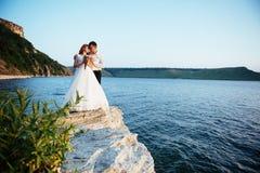 Schöne herrliche blonde Braut und stilvoller Bräutigam auf Felsen Stockfoto