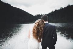 Schöne herrliche Braut, die aufwirft, um sich zu pflegen und Spaß, Luxuszeremonie an den Bergen mit erstaunlicher Ansicht, Raum f lizenzfreie stockfotografie