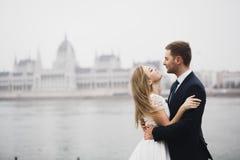 Schöne herrliche Braut, die aufwirft, um sich zu pflegen und Spaß, nahe Budapest-Parlament, Raum für Text, Heiratspaar hat lizenzfreie stockbilder
