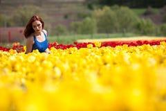 Schöne herrliche Frau im blauen Kleid auf dem Blumengebiet Stockbild
