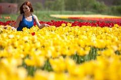 Schöne herrliche Frau im blauen Kleid auf dem Blumengebiet Lizenzfreie Stockbilder