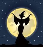 Schöne Hexe, die auf Hintergrund des Mondes steht Stockbild