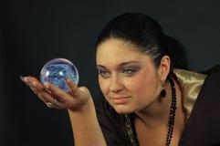 Schöne Hexe mit magischer Kugel stockbild
