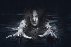 Schöne Hexenfrau, die im Fluss steht Stockbilder