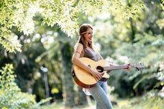 Schöne Hippie, die Gitarre spielt Lizenzfreie Stockfotos