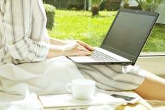 Schöne Hippie-Frau im losen Streifenhemd, das zu Hause, unter Verwendung Personal-Computer sitzt Schreibensdrehbuch des weibliche lizenzfreies stockbild