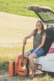 Schöne Hippie-Frau mit der Akustikgitarre, die eine Pause auf Autoreise macht lizenzfreie stockfotos