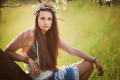 Schöne Hippiefrau, die auf einem Baum sich lehnt stockbild