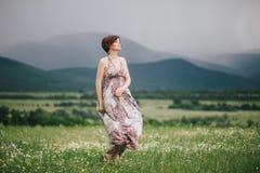 Schöne Hippiefrau, die auf einem grünen Feld mit Bergen auf dem Hintergrund aufwirft lizenzfreies stockfoto