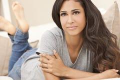 Schöne hispanische Frau, die auf dem Sofa-Lächeln sich entspannt Stockbild
