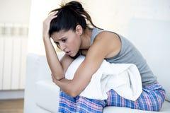 Schöne hispanische Frau im schmerzlichen Ausdruck, der den Bauch erleidet die Monatszeitraumschmerz hält stockfoto