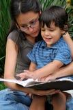 Schöne hispanische Frauen liest zu einem kleinen Jungen Stockbild