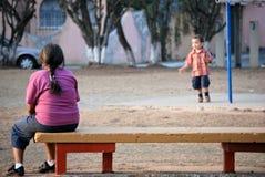 Schöne hispanische Mutter, die ihren Sohn überwacht Lizenzfreies Stockfoto