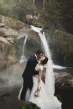 Schöne Hochzeitspaare bleiben auf Stein des Flusses in den szenischen Bergen stockfotos